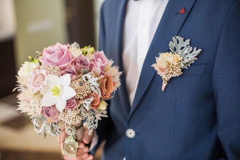 Květina v klopě sladěná se svatební kyticí