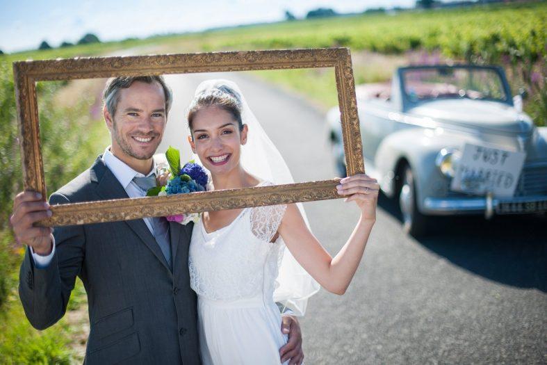 Novomanželé při svatebním focení s prázdným rámem