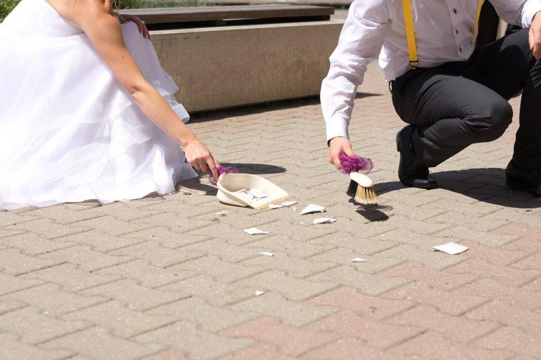 Spolupráce manželů při úklidu střepů na svatbě