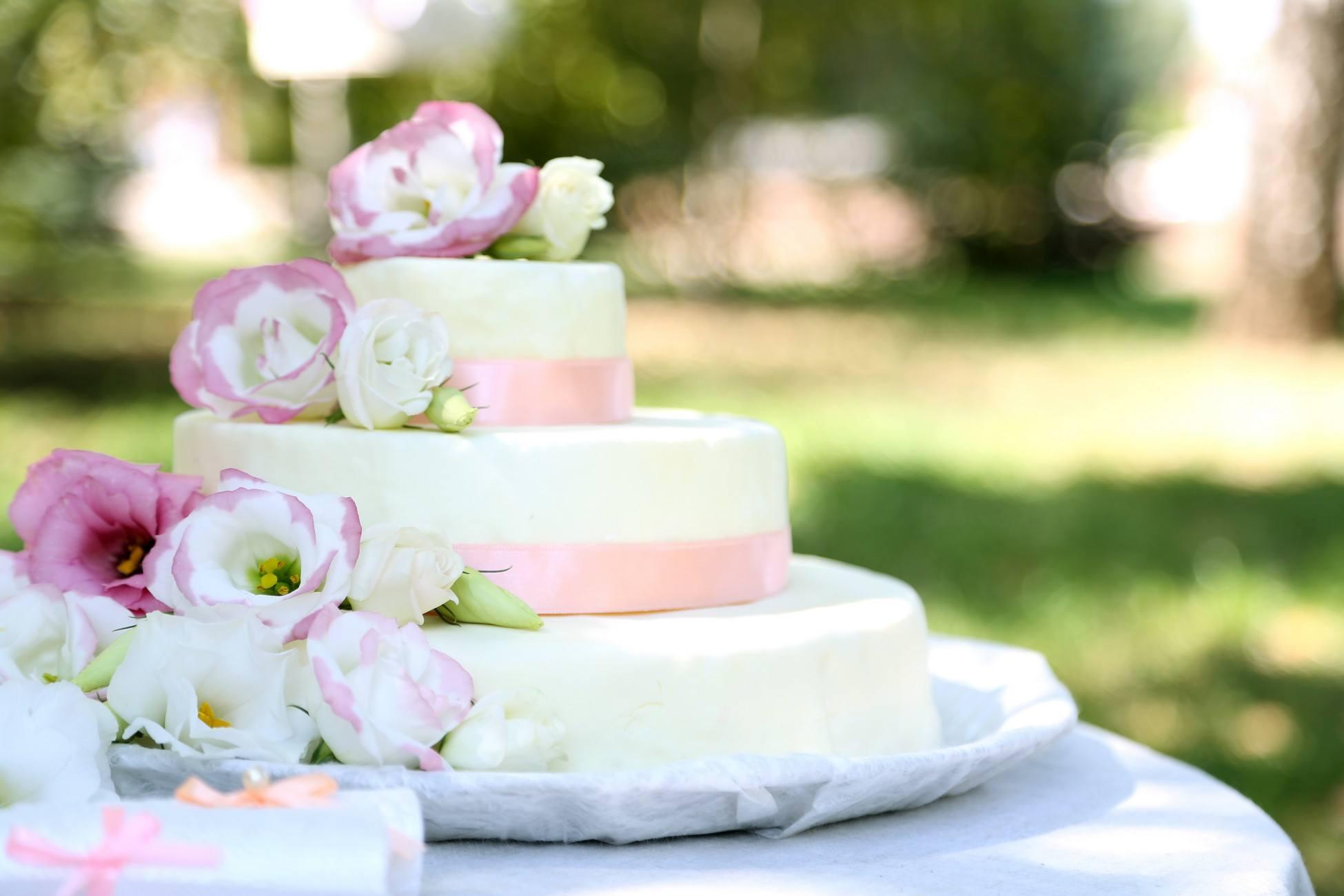 Bílo-růžový patrový svatební dort zdobený květy