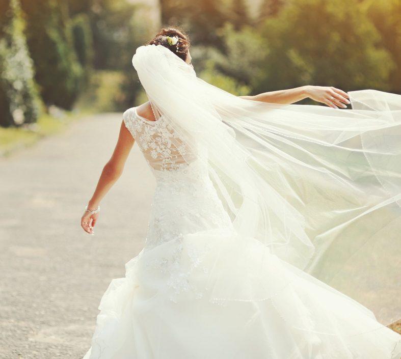Nevěsta v dlouhých svatebních šatech, s drdolem a závojem