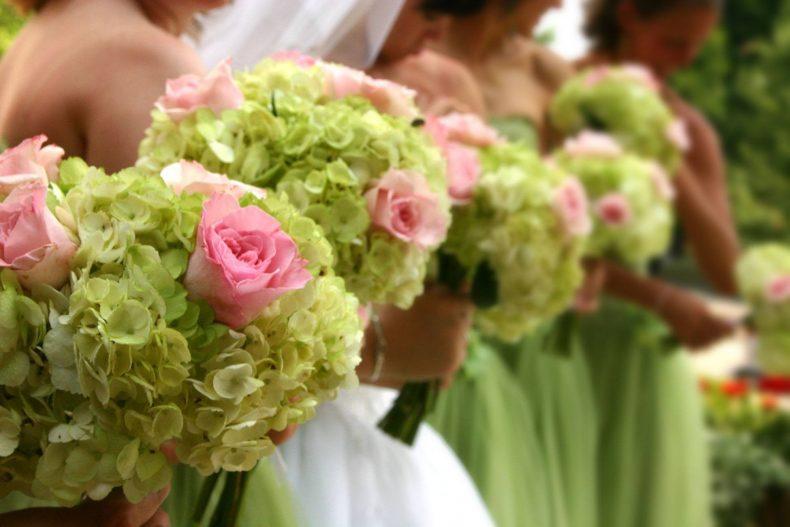 Družičky v tmavě zelených šatech a se zelenými kyticemi