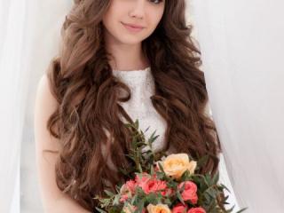 Nevěsta s dlouhými rozpuštěnými vlasy drží kytici růží