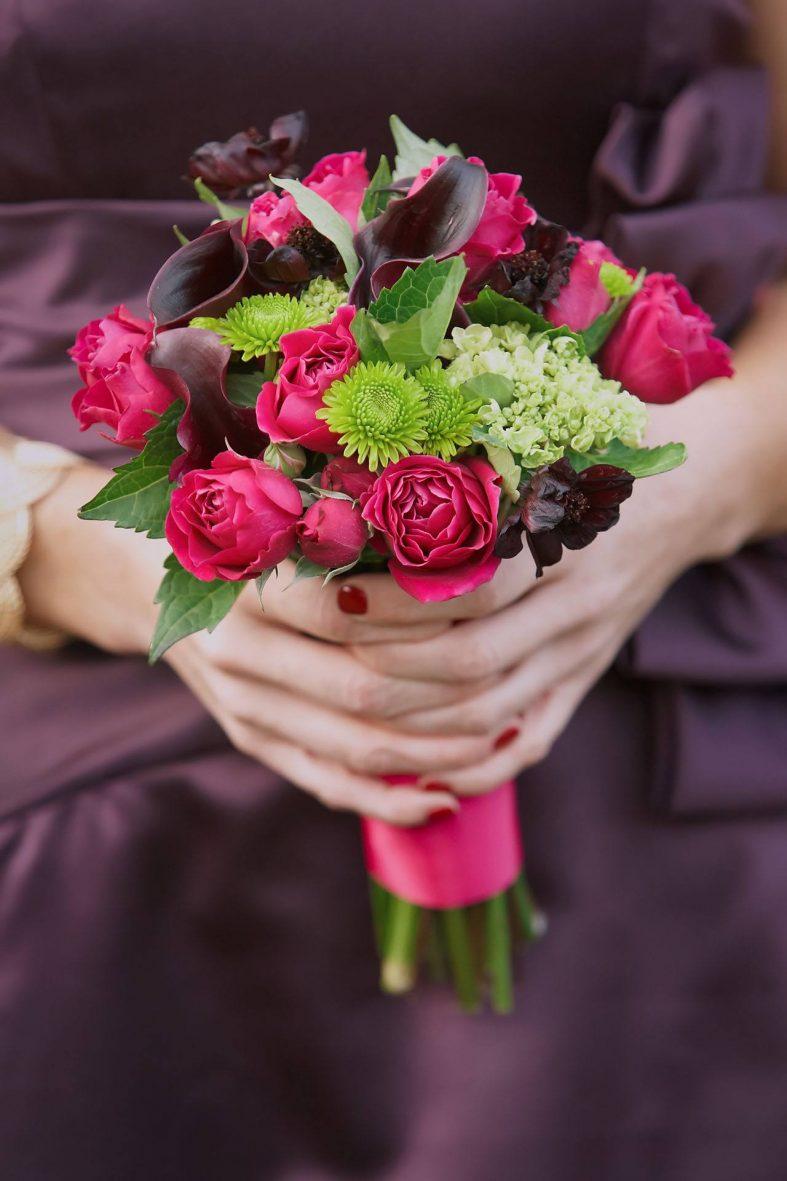 Nevěsta v tmavě fialových šatech s kyticí růží