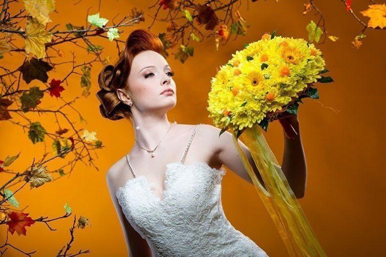 Nevěsta s drdolem drží žlutou kytici gerber