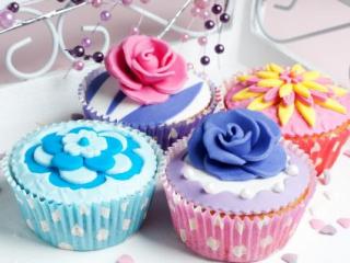 Různě barevné svatební cupcakes zdobené marcipánovými květy.