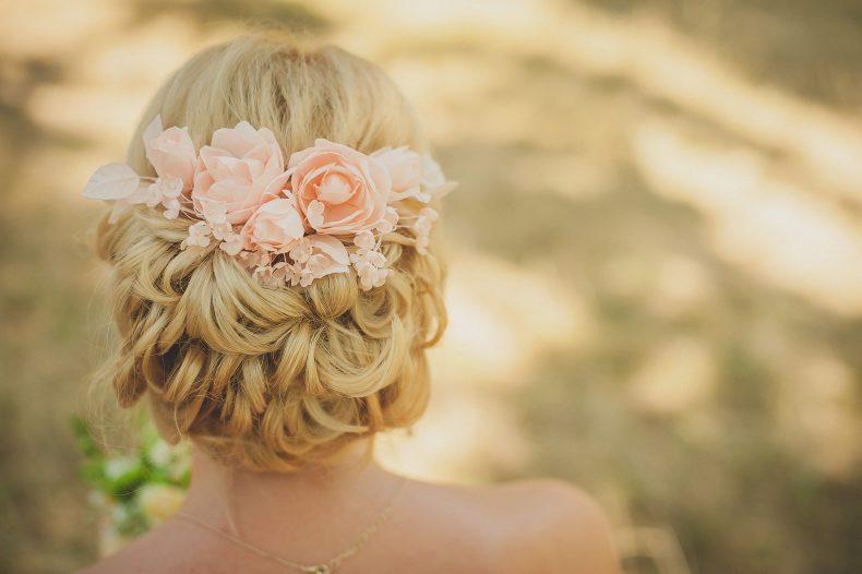 Svatební drdol zdobený světle oranžovými umělými růžemi