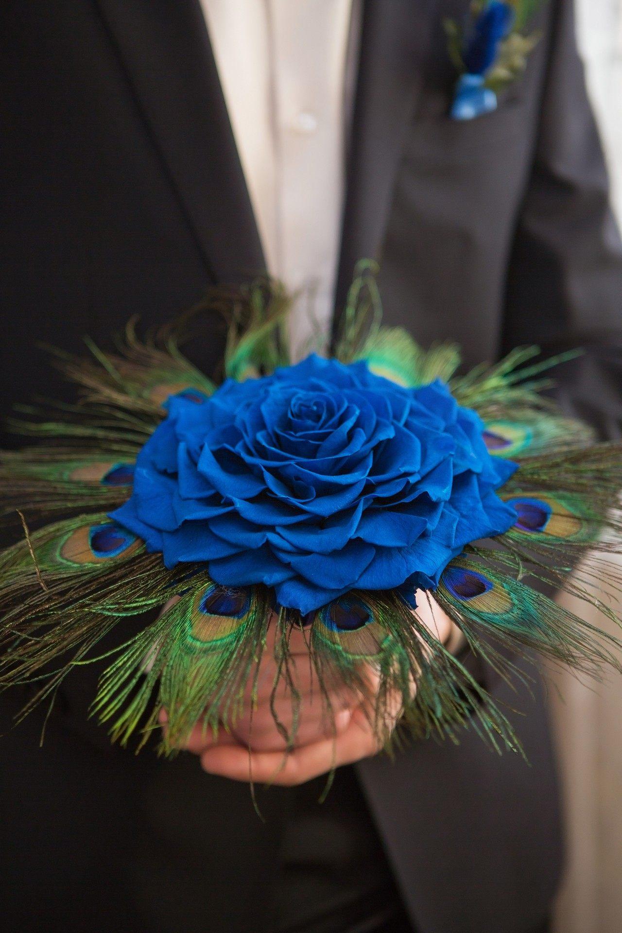 Svatební kytice s velkým květem modré růže a pavím perem
