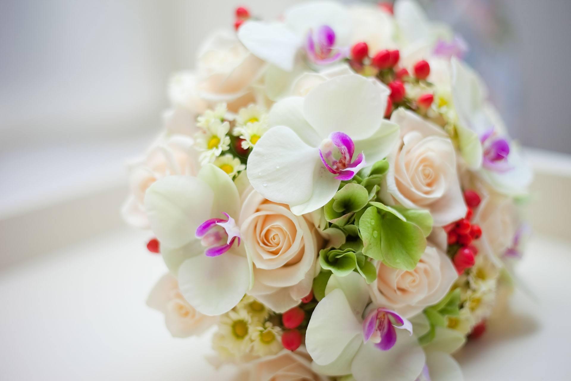 Svatební kytice se světle oranžovými růžemi a bílými orchidejemi