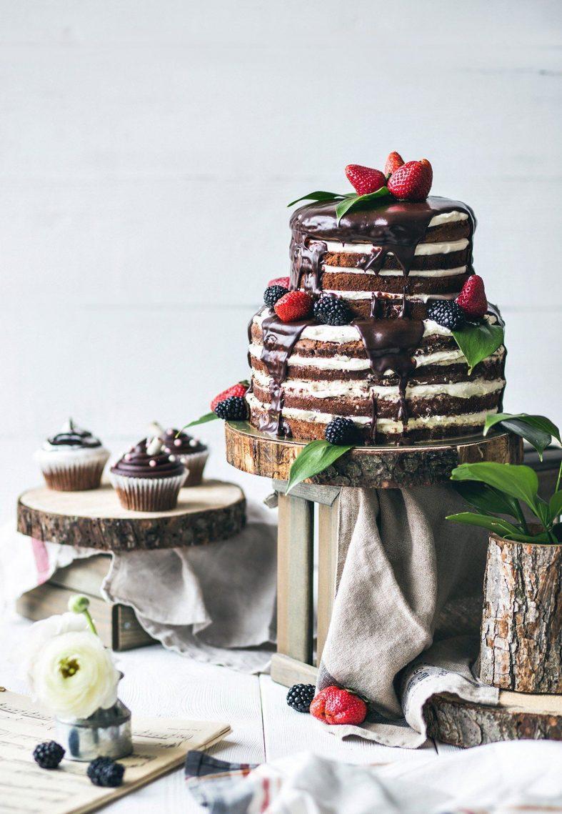 Tmavě hnědý nahý dort přelitý polevou, s jahodami