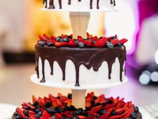 Třípatrový svatební dort politý čokoládou a s lesními plody