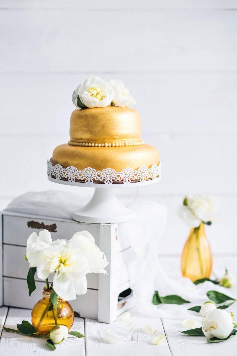 Zlatý patrový svatební dort zdobený pivoňkami